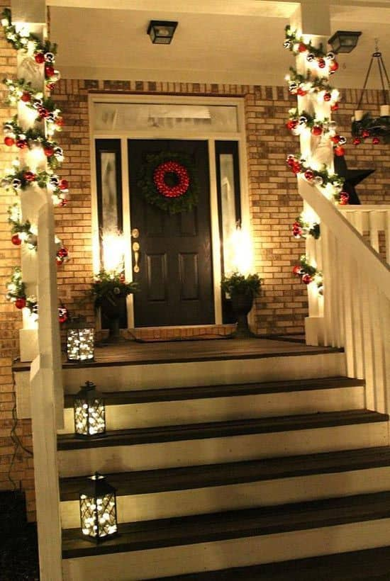 garland and led lights wrap around the porch, lamp on each stair steps #porchIdeas #porch #winter #frontDoorDecor #homeDecor #patiodecor
