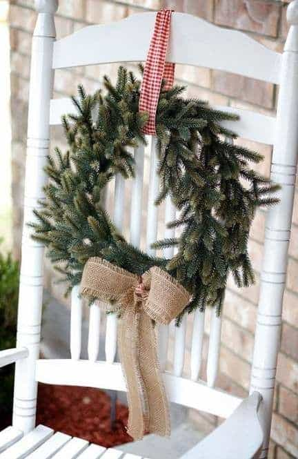white chair decorated with wreath hanging #porchIdeas #porch #winter #frontDoorDecor #homeDecor #patiodecor