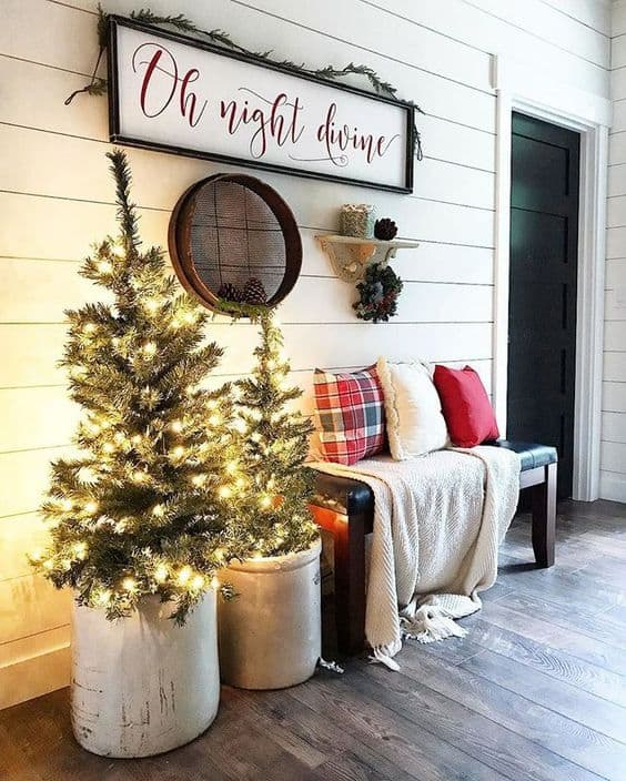 rugs and pillow for a porch bench beside two planters with Christmas tree #porchIdeas #porch #winter #frontDoorDecor #homeDecor #patiodecor  #christmasTree