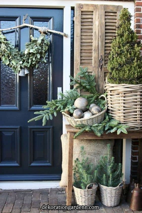 wicker planter for the trees, combined with wicker baskets full of decorations #porchIdeas #porch #winter #frontDoorDecor #homeDecor #patiodecor  #christmasTree