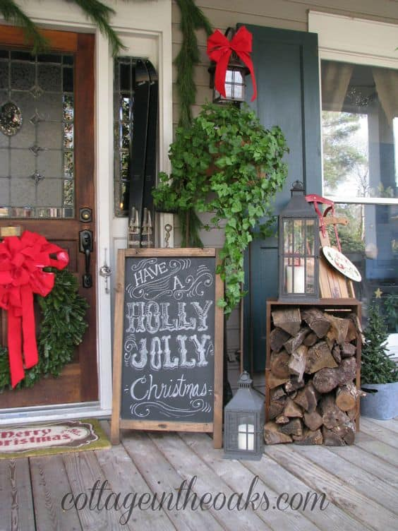 porch decorated with chalg board Christmas message, wreath, trees and a pile of woods  #porchIdeas #porch #winter #frontDoorDecor #homeDecor #patiodecor
