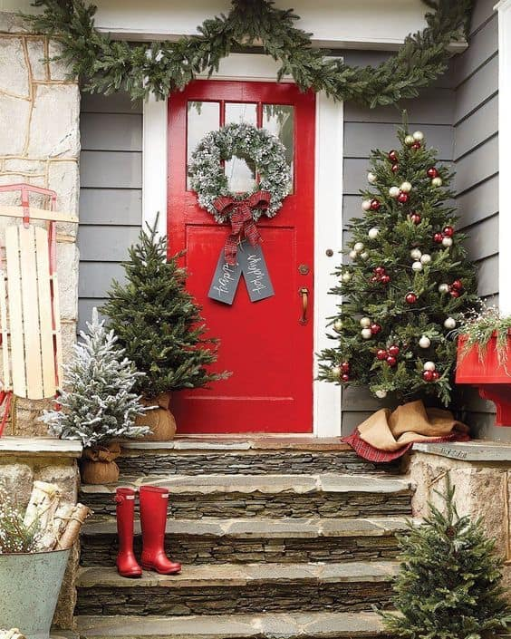 tress leading up the stairs to the front door #porchIdeas #porch #winter #frontDoorDecor #homeDecor #patiodecor  #christmasTree