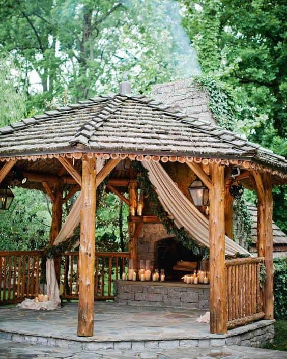a romantic log gazebo with a fire pit, candles, and curtains #gazeboideas #gazebo #pavillion #pavilion #backyardGazebo #candles #firepit #curtains