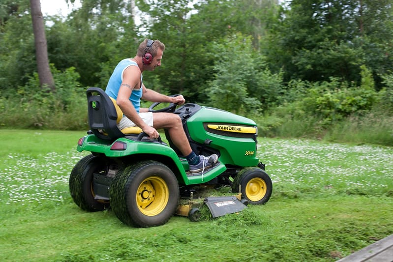 using a John Deere tractor to mow the lawn