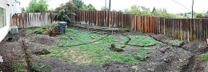 A backyard lawn with trenches dug across and around it.