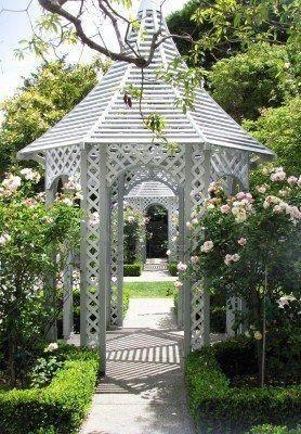 a white lattice gazebo in a blooming garden #gazeboideas #gazebo #pavillion #pavilion #backyardGazebo #flowers