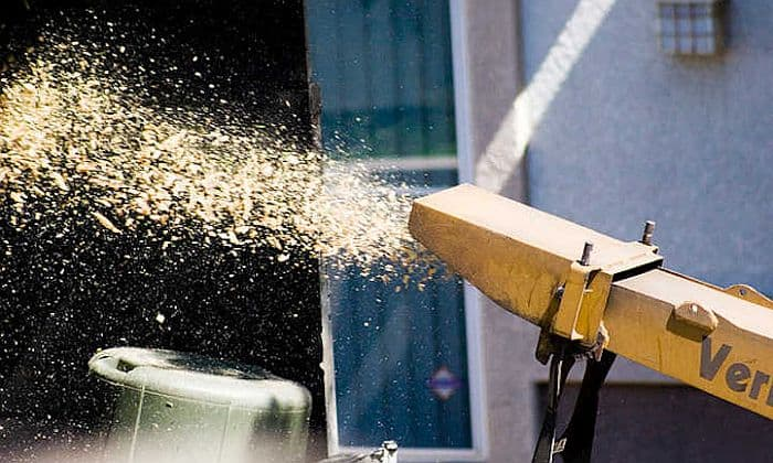 Wood chipper discharge chute discharging wood chips