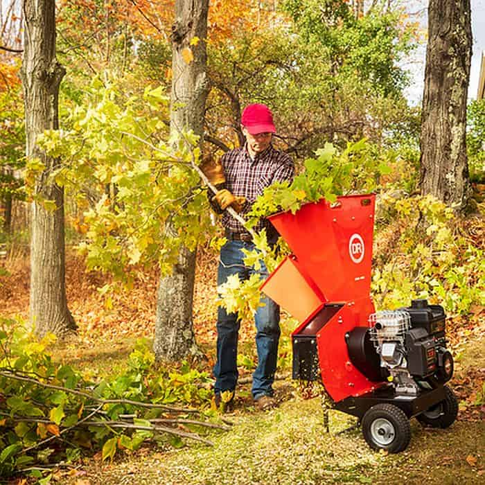 A man chipping wood clipping with a gasoline wood chipper