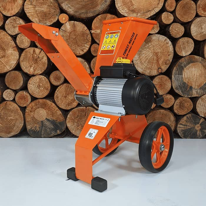 An electric wood chipper with pile of logs in the background