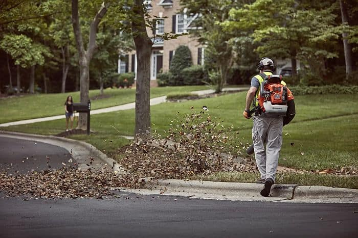 A man blowing off fallen leaves with a husqvarna backpack leaf blower