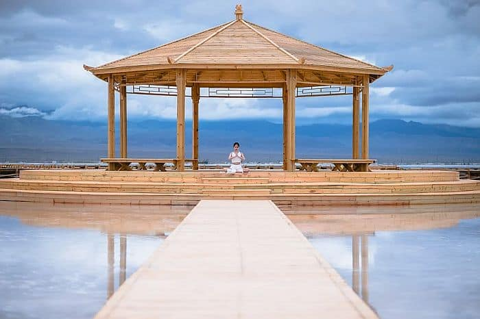 A pavilion by the lake with a young lady doing some meditation