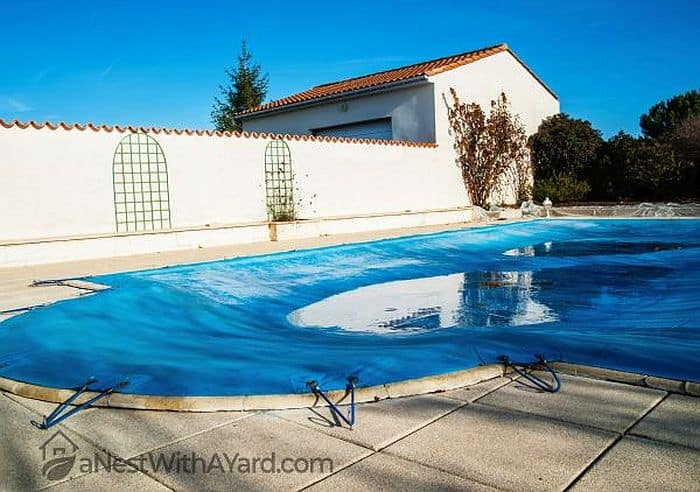 A pool covered with a standard winter cover