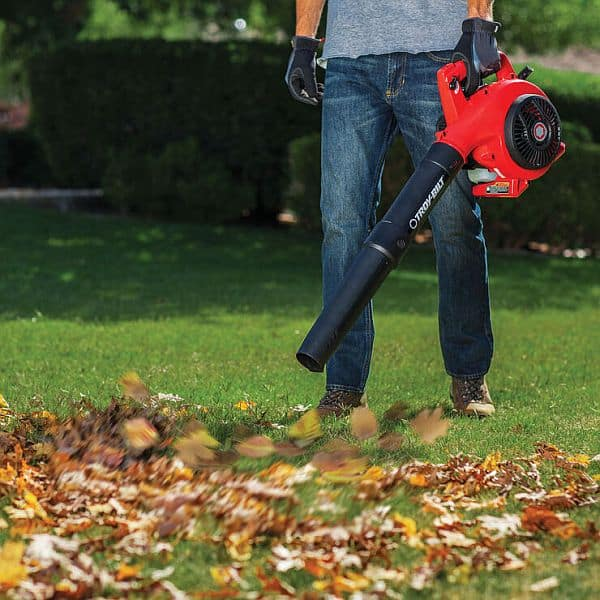 An  handheld leaf blower being used to blow some leaves off the lawn by a man in jeans