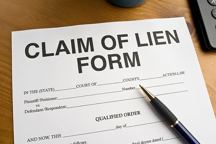 A 'Claim of Lien Form' with a pen