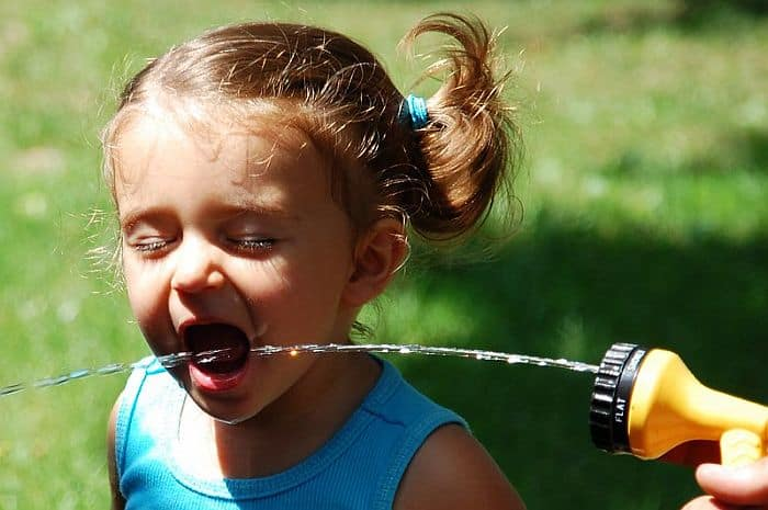 A girl trying to drink water from a garden hose
