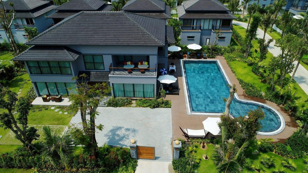 a sprawling mansion with pool and well-maintained landscape and backyard