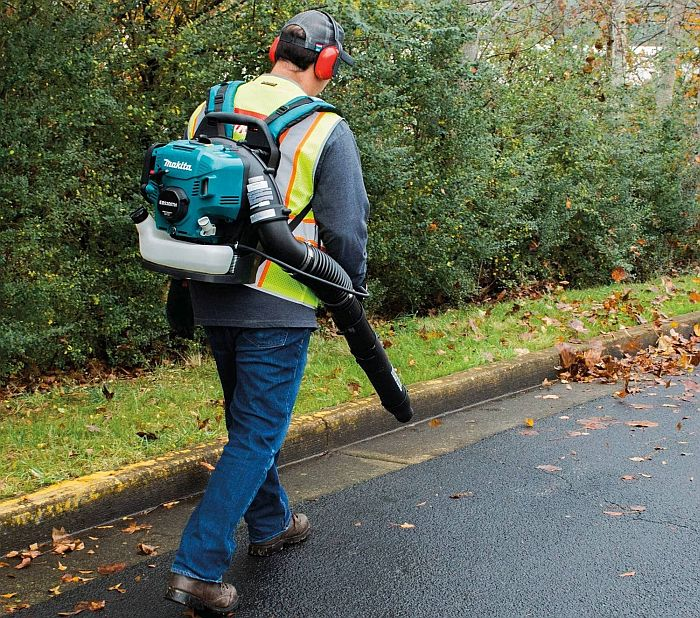 A man using a backpack leaf blower to blow out fallen leaves from the pavement