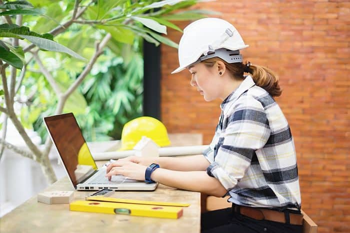 A female engineer working with her laptop upon a makeshift table