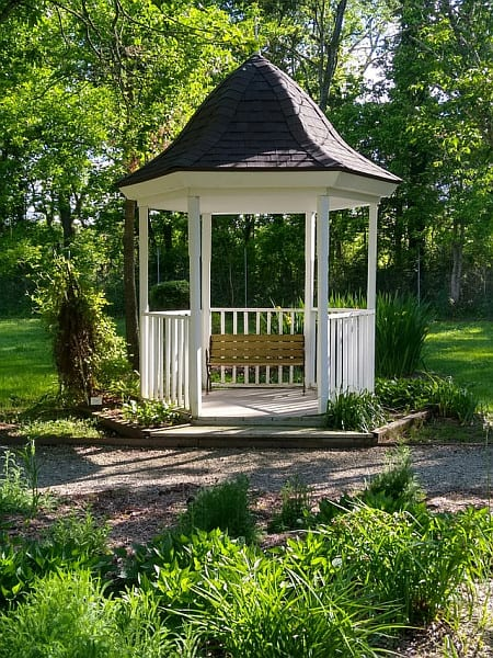A shot of a white hexagonal gazebo with trees in the background