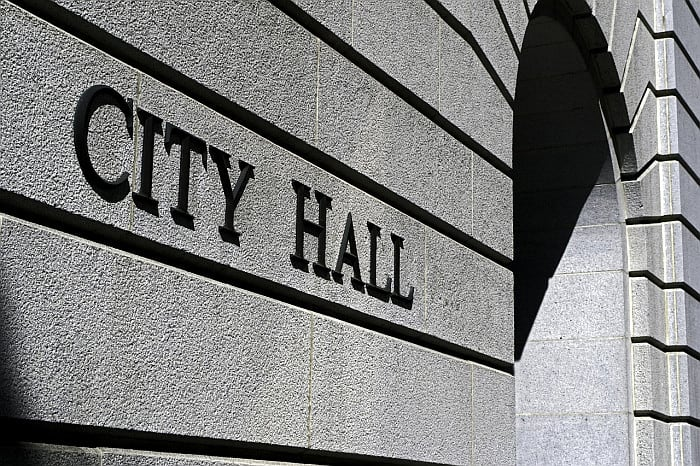 A concrete portion of a building facade with City Hall sign