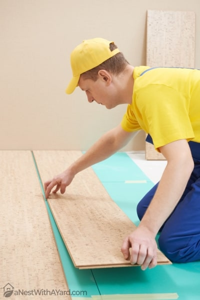 One carpenter worker laying cork boards during shed flooring work