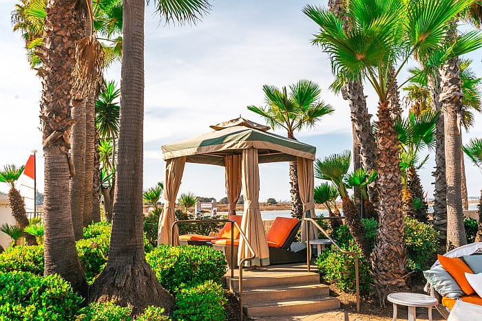 A picture of a square gazebo surrounded by palm trees in a resort