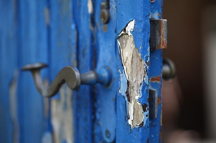 A focused shot on chipped coating on wooden door