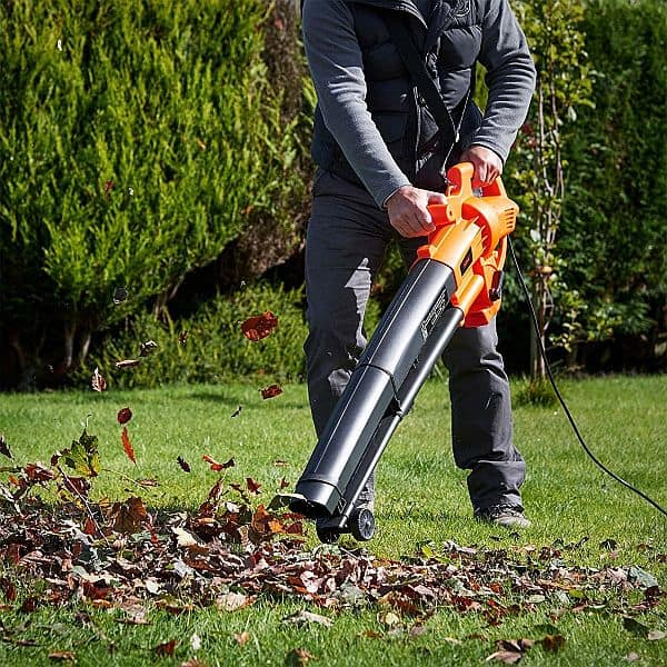 An  handheld electric-powered leaf blower being used to blow some leaves off the lawn