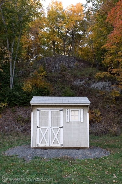A picture of a shed in the backyard with trees in their colorful fall foliage