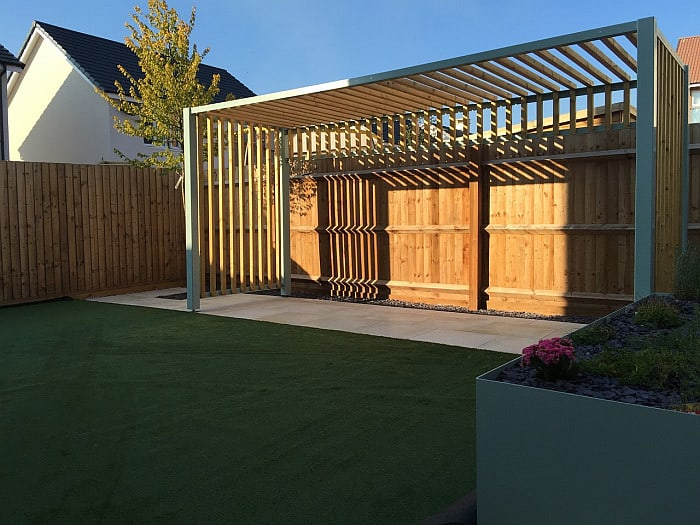 A picture of a pergola by the fence in the backyard