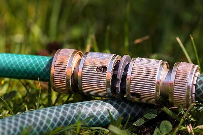 A bronze hose mender attached to a garden hose