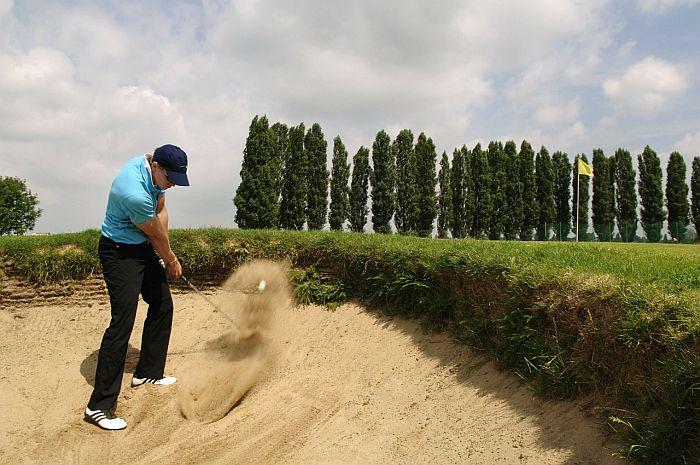 A man in a blue shirt striking a golf ball on sandy part of a golf course