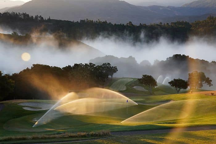 A picture of a golf course in the morning with water sprinklers spraying water across it