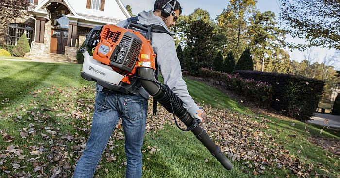 A man blowing fallen leaves off a lawn with a gas powered backpack leaf blower