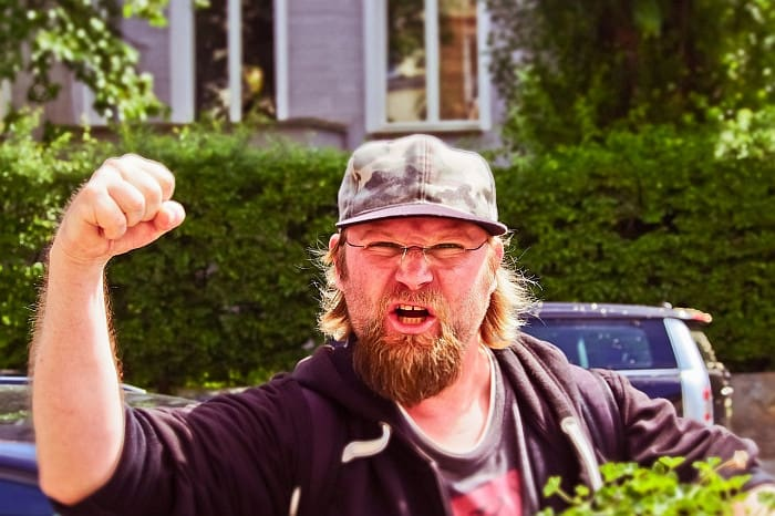 An man raising a closed fist in anger.