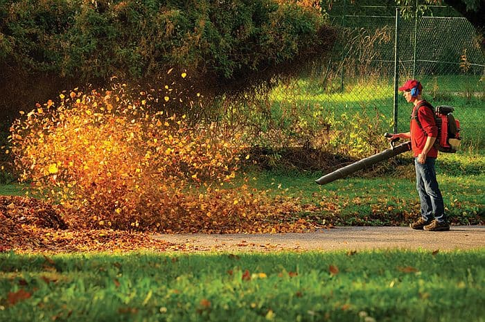 A man in red blowing a pile of fallen leaves of  of pavement in a park with a gas-powered backpack leafblower