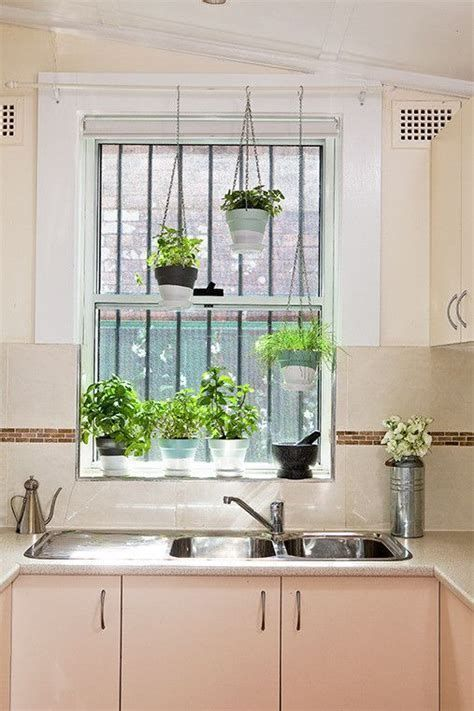 Vertical Herb Garden in the kitchen near a window hung in macrame hangers  #indoorHerbGarden #indoorGardenIdeas #indoorgardendesigns #indoorgardenapartment #apartmentindoorgarden #apartmentgardening
