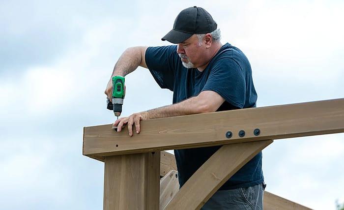 A burly man drilling a screw to a gazebo beam