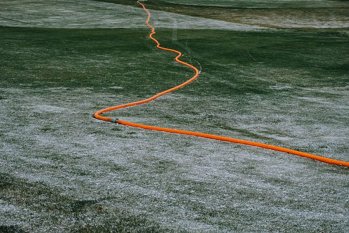 A long garden hose unrolled to the ground