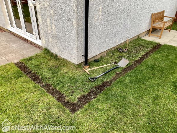 A corner of a lawn with a trench dug up in it