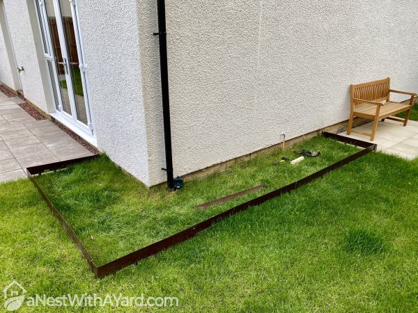 A corner of a lawn with markings for digging