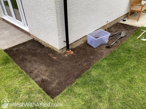 A corner of a lawn with dirt dug up from it