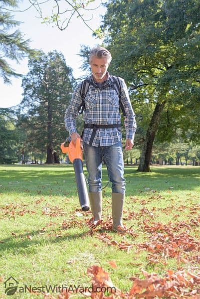 A man operating a handheld leafblower in his yard