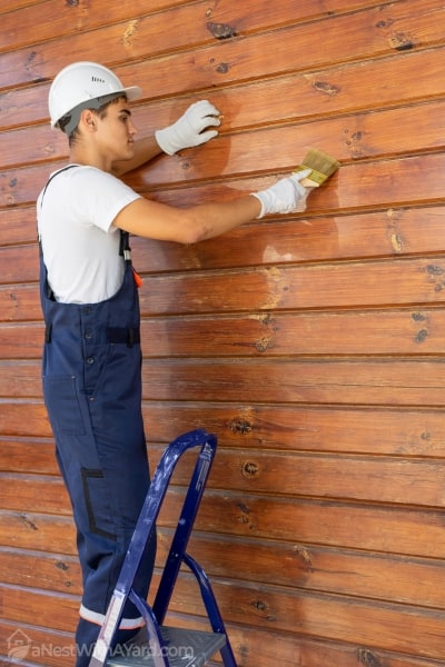 A man cleaning a wooden siding panel