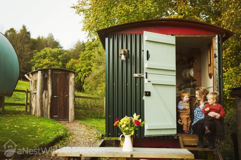 A shepherd's hut with open door beside a path to a small rustic shed, and a woman with two small children seated on the step.