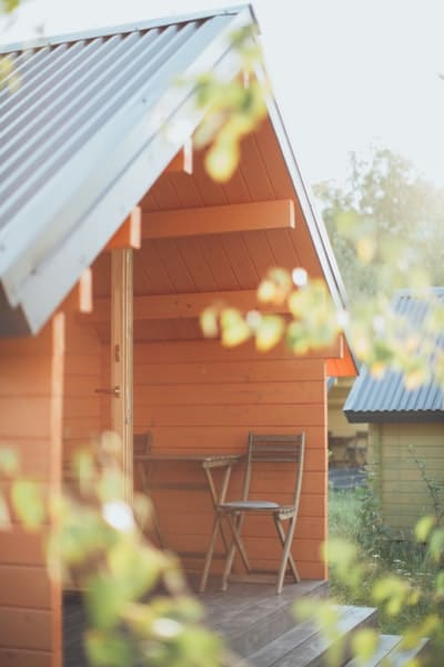 A portrait shot of a wooden shed with wooden chairs and small table in it