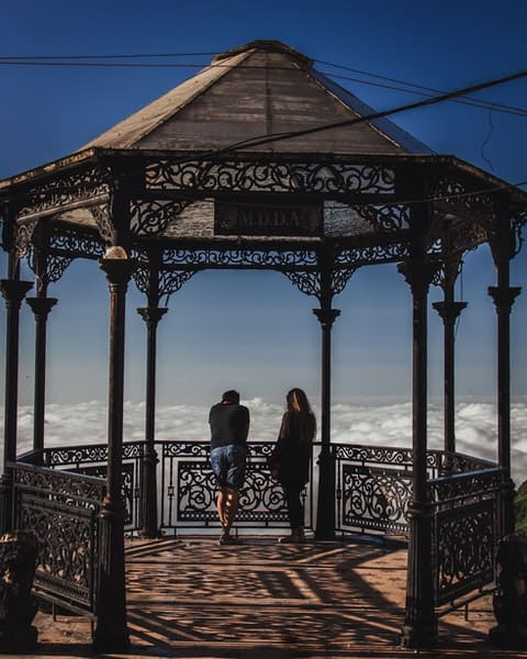A Victorian gazebo on a high altitude location with a sea clouds on the background