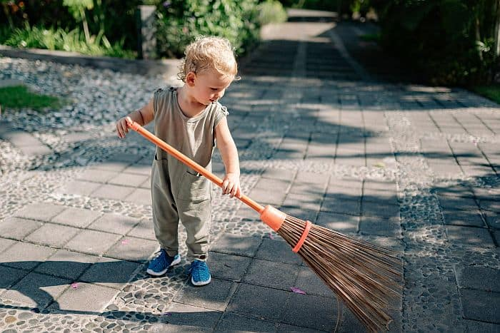 A child sweeping the patio with broomsticks