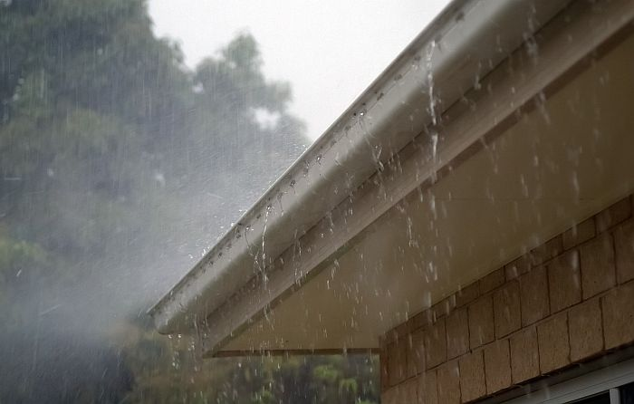 rain water flowing down from a roof gutter in a stormy day