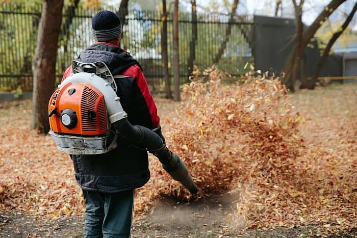 A man using a gas-powered leaf blower to blow out a pile of fallen leaves